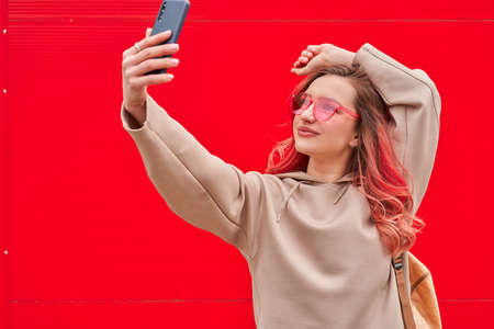 Young blogger woman with pink dyed hairs staying near the red wall and making selfie by smartphone. Outdoor 스톡 콘텐츠