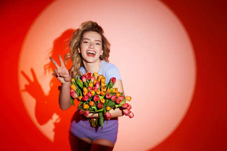 Young woman with bouquet of tulips, dancing in studio. Summerstyle