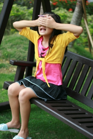 eye: A young girl playing at a greenery field