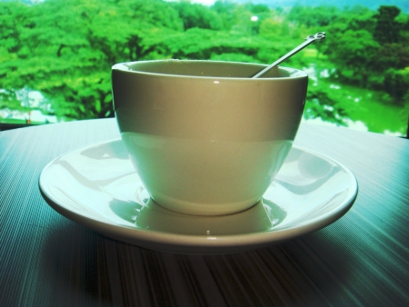 beside: A cup of coffee on table beside a window with nice greenery view