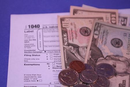 1040 Tax Form on Blue Background with Money Reklamní fotografie