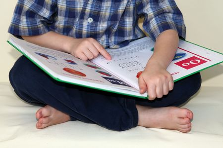 The little boy tries to read the first book. Is photographed on a white background. As the allocated object. Isolated. photo