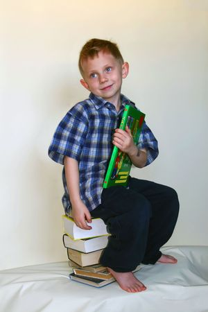 The little boy sits on stop of books with the alphabet in hands - as a symbol of thirst for knowledge. It is photographed on a white background. As the placed object Isolated. photo
