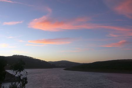 unusually: The sunset has given to the sky unusually beautiful colors. Portugal. Lake.
