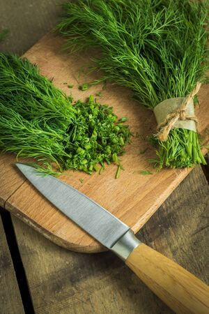 Chopped fresh dill on a cutting Board and a bunch of dill on a wooden backgroung Reklamní fotografie