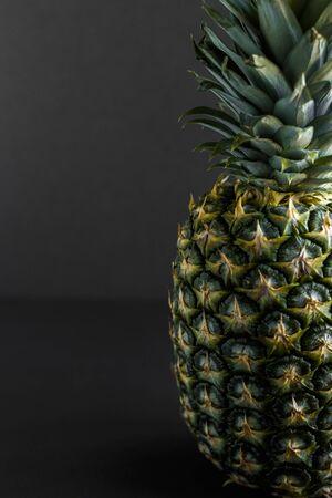 Standing ripe organic pineapple isolated on black. 版權商用圖片