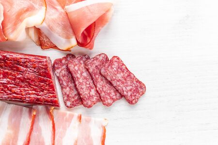 Meat plate with salami, bacon, hamon on a light background. Top view