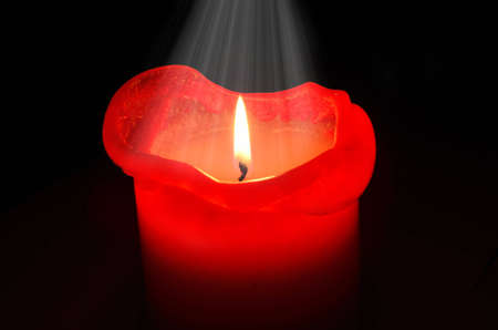 Red candle with a light from above