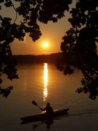 remar: Puesta de sol con un kayak Foto de archivo