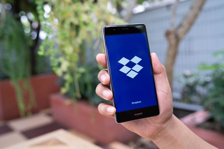 CHIANG MAI, THAILAND - August 08,2018: Man hands holding HUAWEI with Dropbox on screen. Dropbox is a service that gives you access to images, documents and videos online from anywhere.