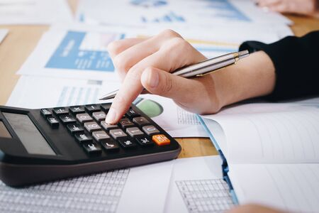 Businesswoman working on calculator to calculate business data the financial report on table.