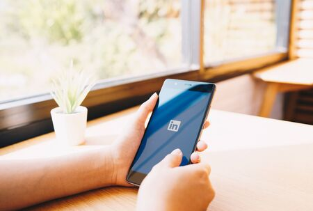 CHIANG MAI, THAILAND - JAN. 19,2019: Woman holding HUAWEI mobile phone with Linkedin application on the screen. Linkedin is a business and employment oriented social networking service. 報道画像