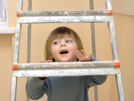 Little boy looking through the step-ladder Stock Photo - 2656317