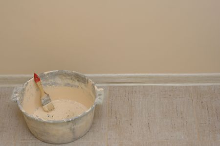 Freshly painted wall — basin with brush on the background of painted wall Stock Photo - 2656314