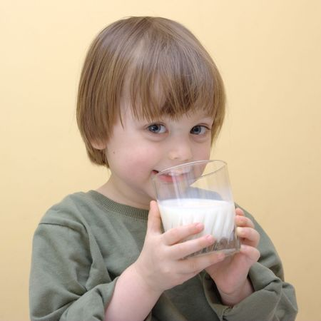 little boy drinking milk from glass