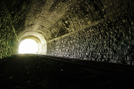 Light at the end of railroad tunnel. Natural lighting.
