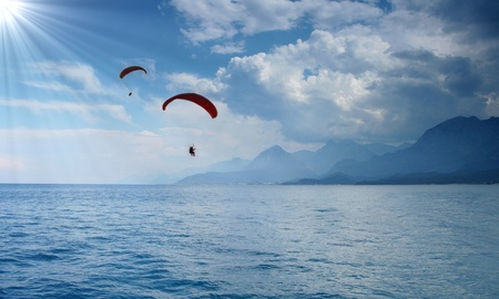 Two paragliders silhouettes on beautiful coastline background