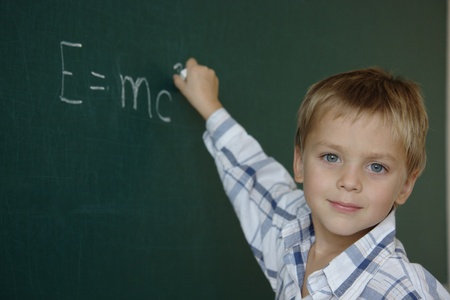 Little boy just writing equation of mass-energy equivalence Stock Photo