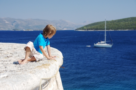 Little boy looking at yacht in the sea photo