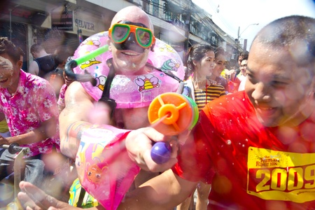 drench: KHAO SAN ROAD, BANGKOK - 2012 APRIL 13: Foreigner with fancy costume pointing his gun