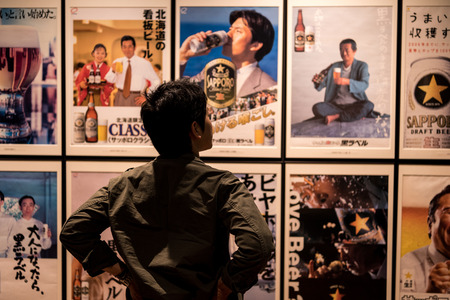 sapporo: SAPPORO, Japan - MAY 05, 2016: A man looking at Sapporo beer advertising posters in Sapporo beer musuem in Sapporo, Hokkaido, Japan Editorial