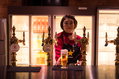 SAPPORO, Japan - MAY 05, 2016: a waitress serve a beer in Sapporo beer musuem in Sapporo, Hokkaido, Japan