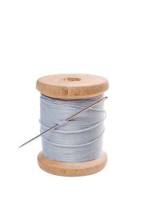 colored spool with threads and needle