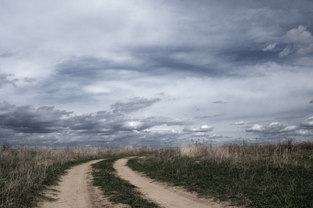 Beautiful rural field road and the cloudy sky photo