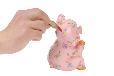 Male hand putting coin into a piggy bank isolated on white photo