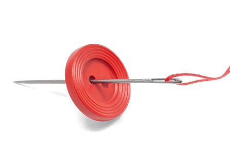 Red thread, button and needle isolated on white
