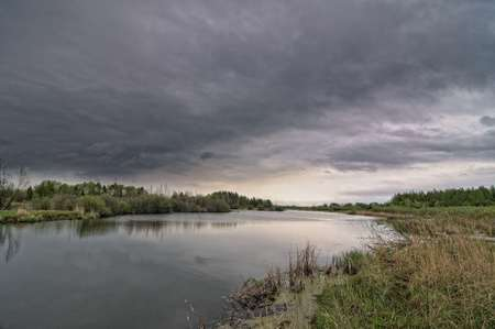 A river landscape with dark stormy sky