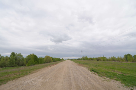 Gravel country road and cloudy stormic sky Stock Photo