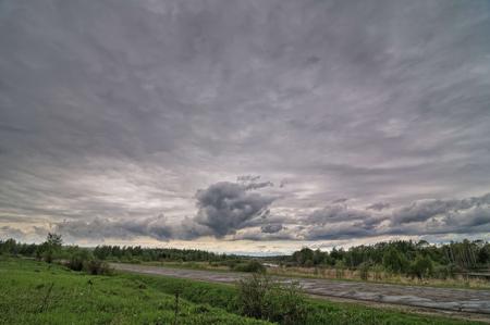 Old country asphalt road, storm dark sky Stock Photo