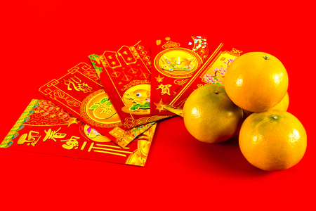and is favorable: Four oranges and red envelope with chinese blessing word are gift for chinese new year festival