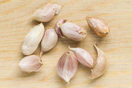 garlic clove: Garlic clove on wood chopping block.