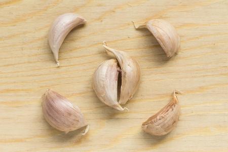 clove: Garlic clove on wood chopping block.