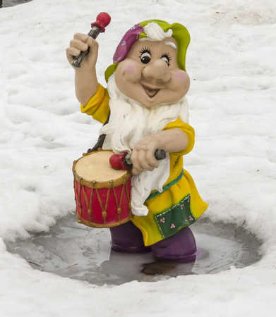 Sculpture of a little gnome with a drum. On the background of snow. Overcast weather.