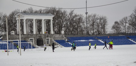 Kirovsk, Russia, March 17, 2019. Children play football in the stadium on the snow. Editorial