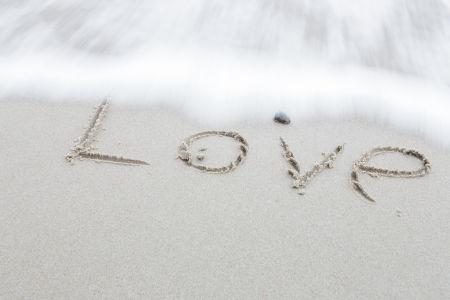 wording Love on sand beach background photo
