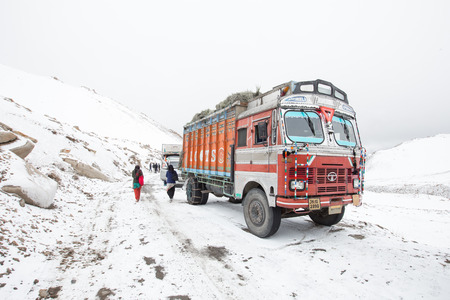Ladakh, India - April, 17, 2014: Truck on the snow mountain and high altitude Khardung La Pass-Leh road, state of Ladakh, Indian Himalayas, India
