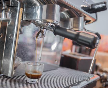 prepares espresso in his coffee shop; close-up photo