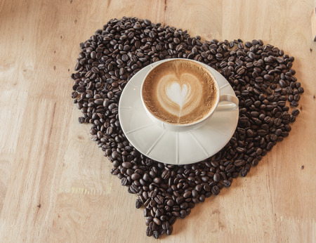 Coffee cup with coffe bean heart on table Stock Photo