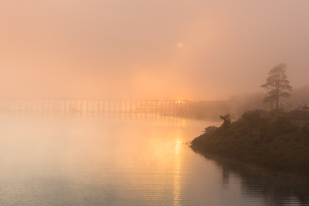 gr: The sun behind fog at morning with the longest wood brigde in Thailand Stock Photo