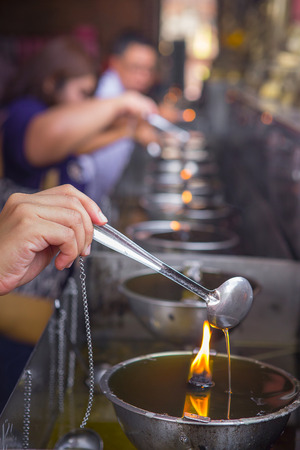 sacramental: Oil filling in Thai style metal candle in Thai temple Stock Photo