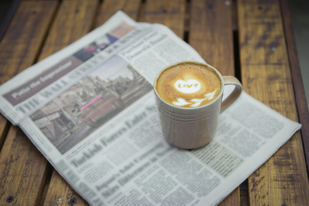broadsheet newspaper: A newspaper and a cup of coffee on a wooden table