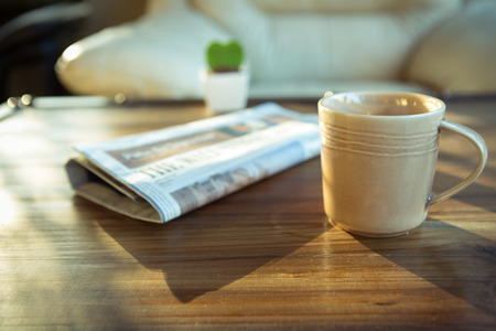 broadsheet newspaper: a cup of coffee with newspaper on table at coffee shop