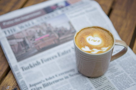 broadsheet: A newspaper and a cup of coffee on a wooden table