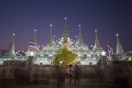 gr: Thai pagoda at twilight of Magha Puja Days. Light of candles waving around the pagoda. Wat Asokaram, Sumutpakran , Thailand Stock Photo