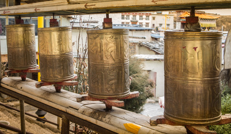 Buddhist prayer wheels in Tibetan monastery with written mantra. photo