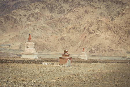 gr: Stupa at sand field with mountain in Leh  India